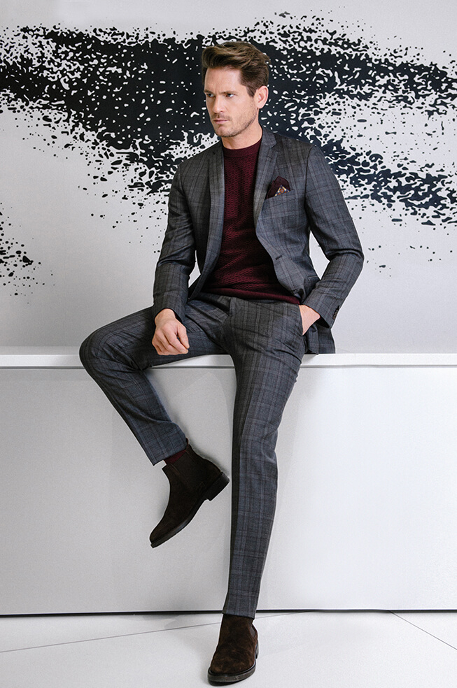 Man wearing suit with a casual jumper